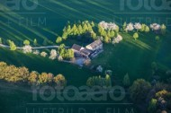 Ein Grundstück mit Häusern steht inmitten einer gro�en Wiese mit einigen Bäumen und Wegen.