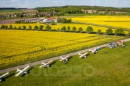 FLugzeuge stehen nebeneinander auf einem Flugplatz.