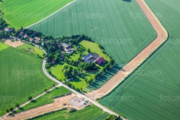 Ein kleines Dorf liegt direkt in einem groÃ?em Feld.