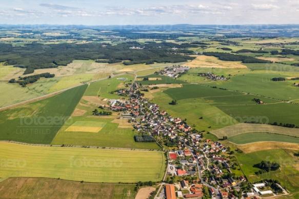 Eine Häuserlandschaft inmitten von Feldern und Wiesen.