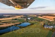 Blick aus dem Flugzeug auf Wiesen, Wälder und Felder in der Abenddämmerung