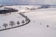 Schneeverwehungen auf dem Feld, Wälder und ein Dorf