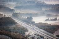 Eine Autobahn umhüllt in eine Nebeldecke.