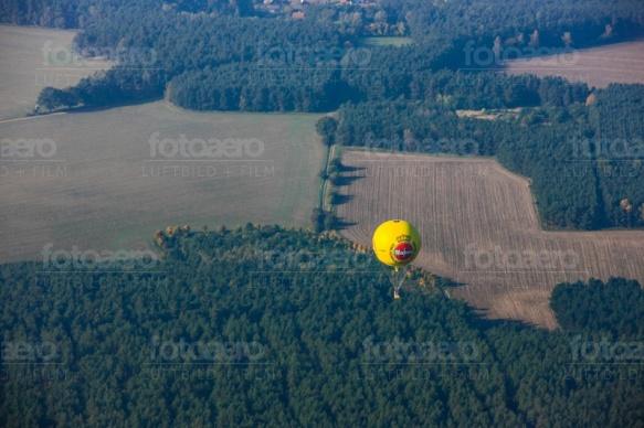 Warsteiner Ballon fliegt über wald und Feld.