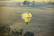 Ein Drewag Heisluftbalon fliegt über ein sonniges Feld.
