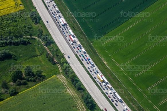 Eine Autobahn, die entlang eines groÃ?en Feldes geht.
