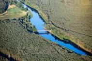 Eine Brücke über ein Fluss umgeben von Wäldern