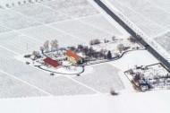 Dreiseitenhof umgeben von Feldern im Winter