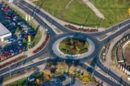 Kreisverkehr umgeben von Grünfläche und Autos.