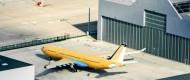 Gelbes Flugzeug steht auf Flughafen.