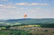 Ein Gleitschirmflieger fliegt über Felder und Wiesen.