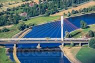 Noch nicht fertiggestellte Brücke, die über einen strahlend blauen See verläuft.