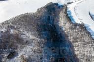Verschneiter Waldabschnitt und Felder im Winter