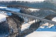Blick auf eine befahrene Brücke entlang von Hügeln und Tälern.
