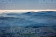 Neblige Hügellandschaft mit Wälder, Felder, Wiesen und kleinen Ortschaften