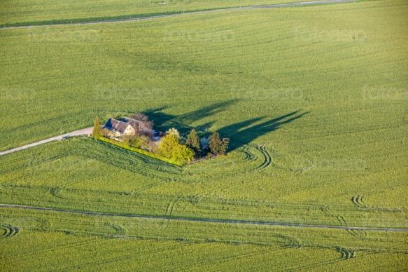 Ein Haus mit Garten inmitten von einem groÃ?en Feld.