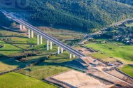 Noch nicht fertiggestellte Brücke, die entlang eines Waldes führt.