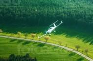 Ein Flugzeug fliegt einen groÃ?en Bogen, entlang des Waldrandes.
