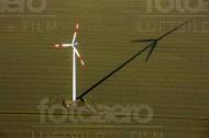 Ein Windrad welches durch die Sonne einen groÃ?en Schatten abbildet.