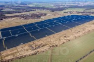 Gro�es Solaranlagenfeld inmitten von Wäldern und Wiesen.