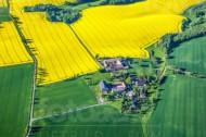 Ein kleines Dorf inmitten von Feldern und Wegen.